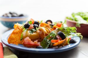 Mexican Velveeta Nachos on a blue plate garnished with lettuce, tomatoes and black olives.When you just want a quick cheesy snack, convenience meets flavor in this colorful dish.