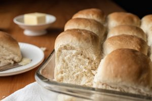 Pan of dinner rolls with one removed. Plate with butter knife and butter in the background.