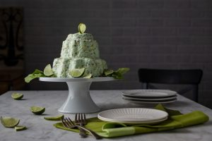 Lime Jello Salad on a cake stand with limes and lettuce as garnish