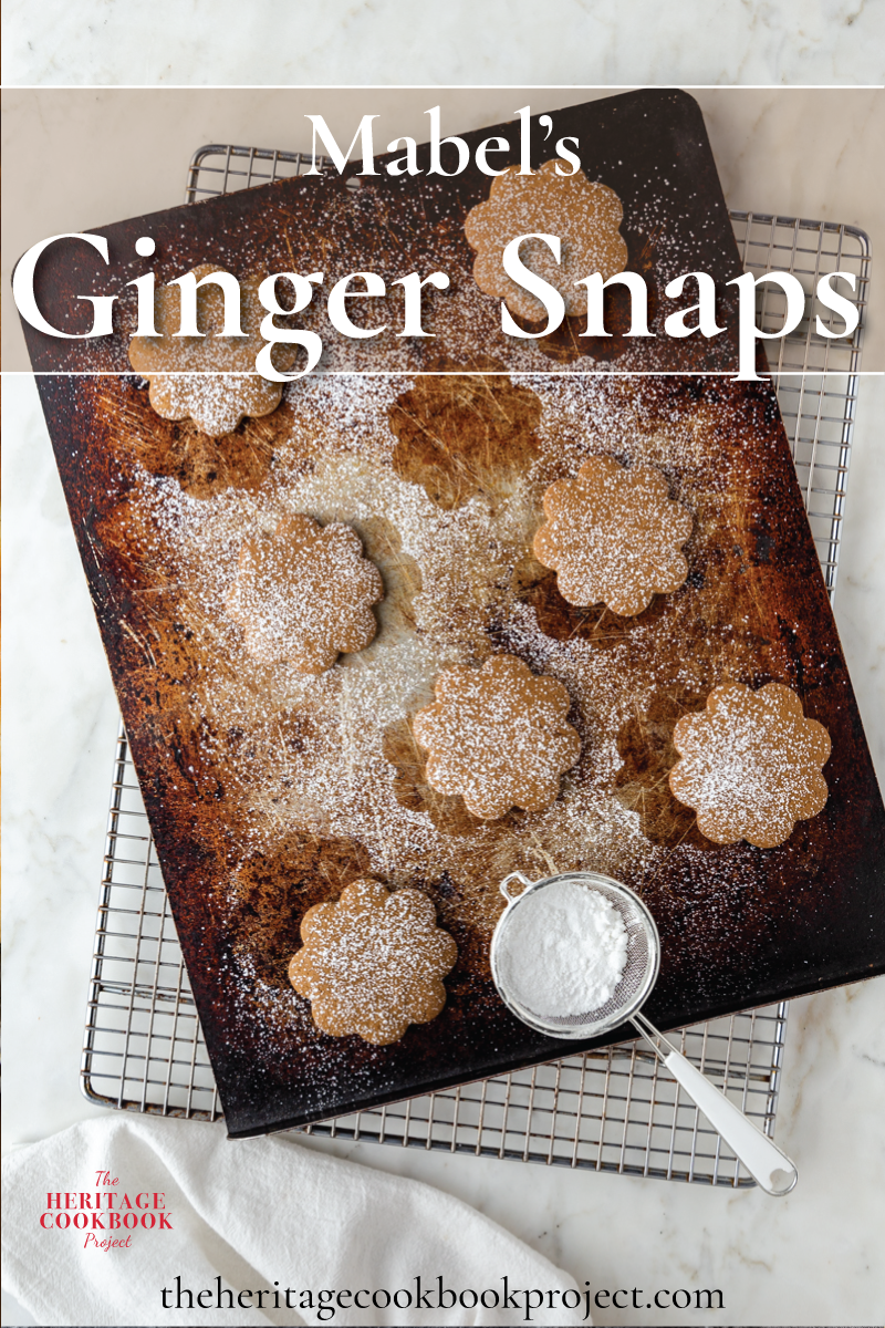 Mabel's Ginger Snaps cookies on a baking sheet with powdered sugar sprinkled over the top.