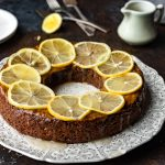 Spice English Crumb Pudding with lemon slices and lemon cream on a filigreed platter.