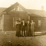 Image of the Arrington house with 4 people in the front