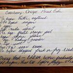 Hand written recipe card for cranberry orange pound cake recipe card sitting on wicker basket.
