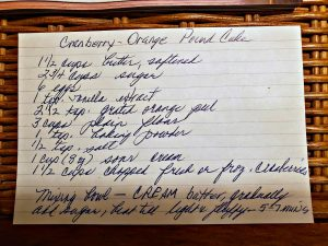 Hand written recipe card for cranberry orange pound cake recipe card sitting on wicker basket.