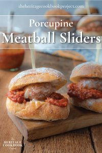Porcupine Meatball Sliders sitting on a small cutting board with more sliders in the background.
