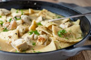 Chicken and Dumplings in cast iron skillet and serving spoon.