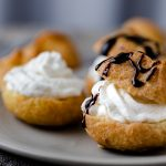 Cream puffs with whipped cream and a chocolate drizzle over the top.
