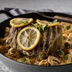 Pot Roast in Sour Cream with mushrooms and lemons in a grey Dutch oven with a serving fork laying across the pan.