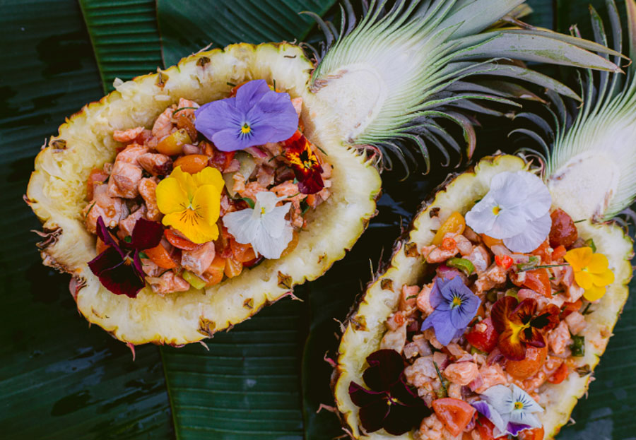 sinigang poke served in the pineapple halves with edible flowers on banana leaves