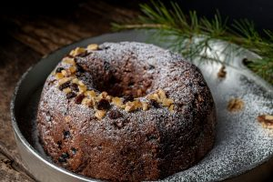 Fruit Cake Bundt cake on a silver platter with a pine bow in the background. Decorated with raisins, candied orange peel, and walnuts.
