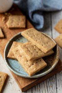 Scotch Shortbread Cookies pile on plate with coffee in the backgroun