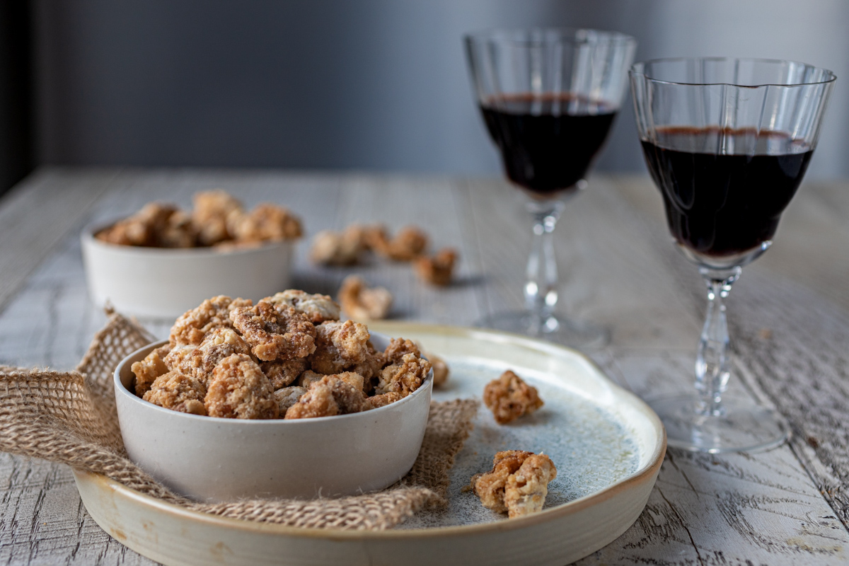 Candied Swedish Nuts in a white bowl with wine in the background.